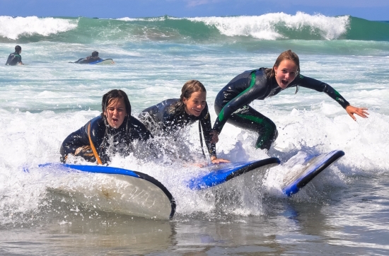 girls-surfing-together-bilbao-teens-surf-camp