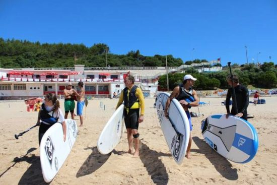 lisbon-surf-camp-cascais-carying-sup-boards-to-water