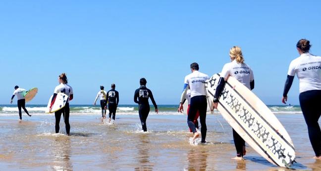 lisbon-surf-camp-cascais-surfer-group-entering-water
