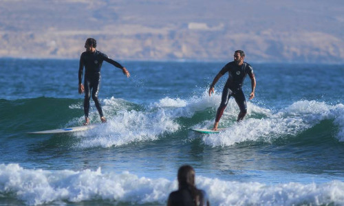 Two surfers surfing in Morocco