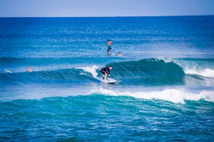 Riding a wave at Puaena Point Beach